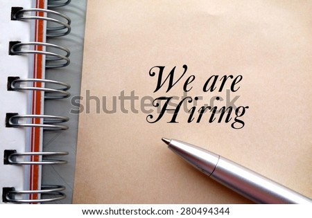 We are hiring text write on paper as background with pen and book - stock photo