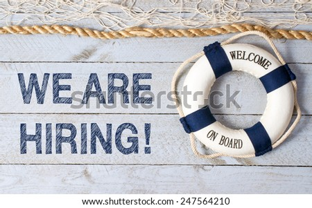We are hiring ! - Welcome on Board - Lifebuoy with fishnet and blue text on wooden background - stock photo