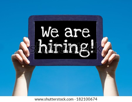 We are hiring ! Woman holding blackboard over blue background with text We are hiring ! - stock photo