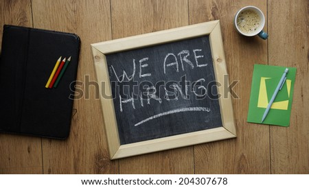 We are hiring written on a chalkboard at the office - stock photo