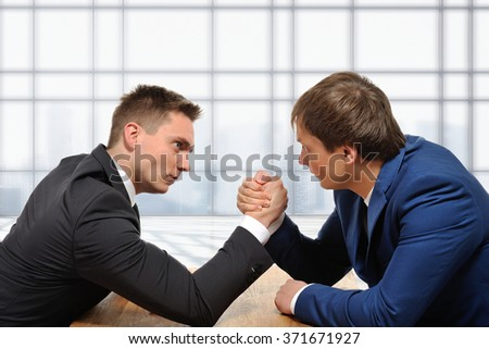 We are in a competitive business. Two businessmen arm wrestling. Modern office background.