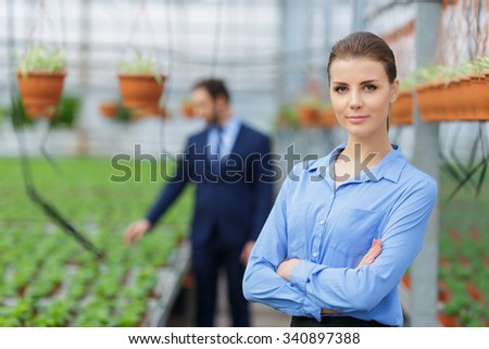 We are leaders. Pleasant attractive confident businesswoman folding her hands and standing in  her greenhouse with the colleague working in the background - stock photo