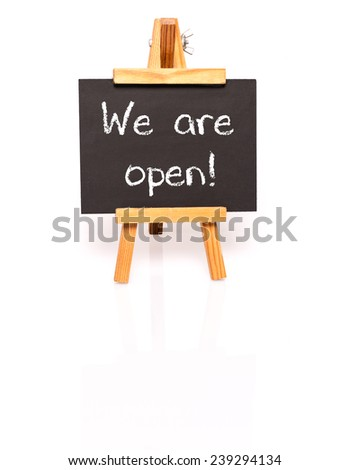 We are open. Blackboard with text and easel. Photo on white background with shadow and reflection. - stock photo