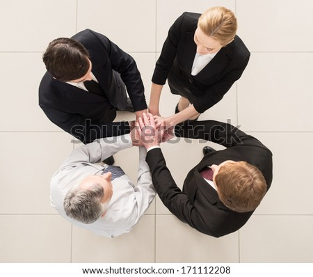 We are team! Top view of four people in formalwear standing close to each other and clasping their hands together - stock photo
