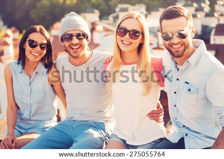 We are the best friends! Four young cheerful people bonding to each other and smiling while sitting on the roof of the building together - stock photo