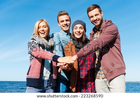 We are the best friends. Four young happy people bonding to each other and holding hands together while standing on the beach with river in the background - stock photo