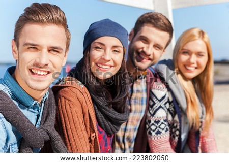 We are the best friends! Group of young happy people bonding to each other and smiling while sitting at the riverbank - stock photo