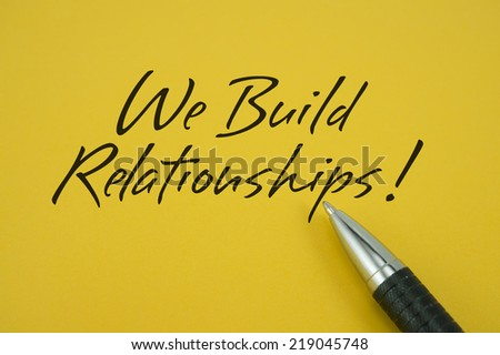 We Build Relationships! note with pen on yellow background