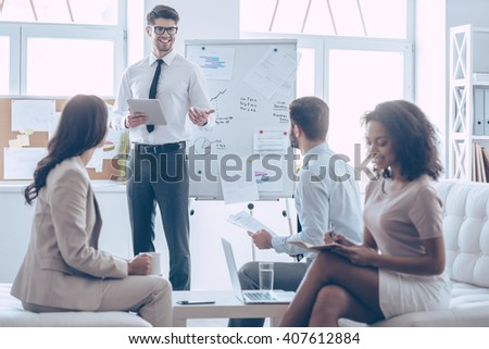 We can do it! Young handsome cheerful man holding digital tablet and discussing something with his coworkers with smile while standing in office  - stock photo