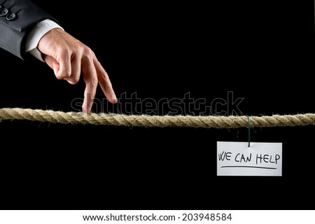 We Can Help concept with a hand written note bearing the words hanging on a wire from a rope suspended over a black background with a businessman walking his fingers along it like a tightrope. - stock photo