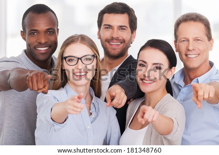 We choose you! Group of cheerful business people in casual wear standing close to each other and pointing you - stock photo