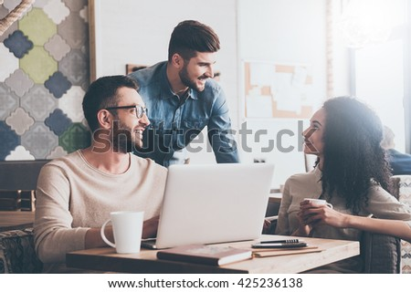 We did it! Young cheerful people looking at each other with smile while sitting at the office table on business meeting   - stock photo