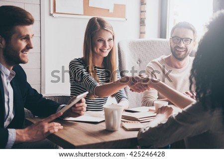 We have a deal! Two beautiful women shaking hands and looking at each other with smile while sitting at the business meeting with their coworkers - stock photo