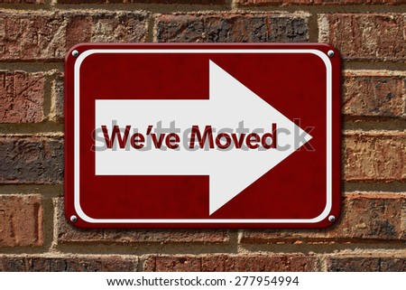 We have Moved Sign,  A red sign with the word We've Moved with an arrow on a brick wall