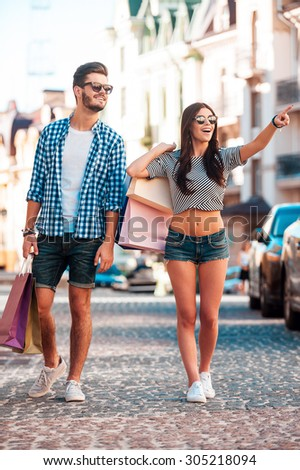We have to visit that shop! Full length of young loving couple holding shopping bags and looking away while walking along the street  - stock photo
