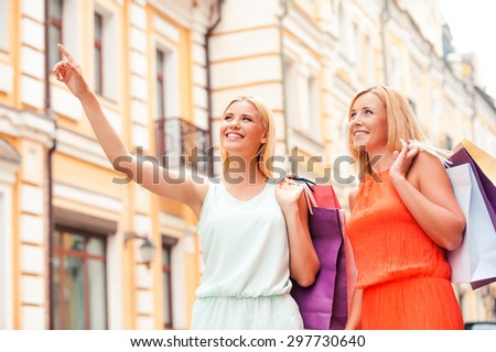 We have to visit this shop. Low angle view of cheerful young woman and her mother carrying shopping bags and looking away while walking outdoors - stock photo