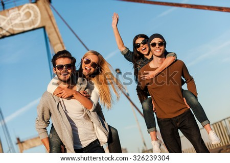 We just want to have fun! Two handsome young men piggybacking their girlfriends and smiling while walking along the bridge - stock photo
