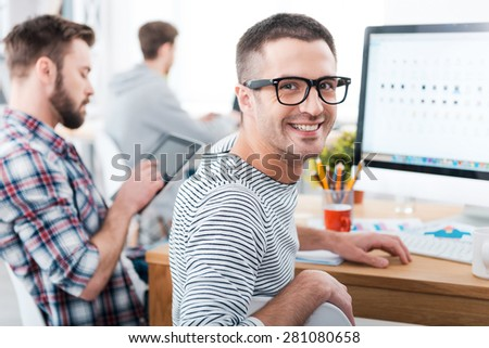 We keep it casual in our office. Happy young man looking over shoulder and smiling while sitting at desk with his colleagues working in the background - stock photo