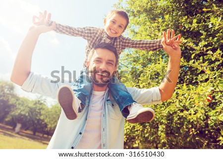 We like spending time together! Low angle view of happy little boy stretching out hands while his father carrying him on shoulders - stock photo