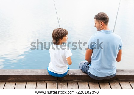 We love fishing together. Rear view of father and son fishing while sitting on quayside together - stock photo