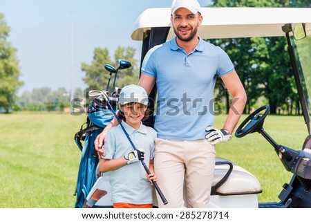 We love golf! Smiling young man embracing his son while leaning golf cart - stock photo