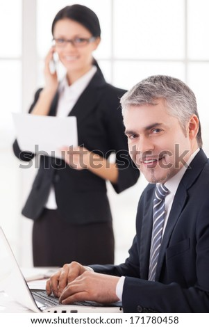We love our job. Cheerful mature businessman working on laptop and smiling at camera while beautiful woman in formalwear talking on mobile phone on background