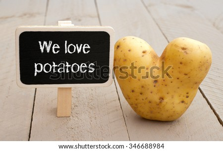 We love potatoes - little chalkboard with text and heart shaped potato on wooden background - stock photo