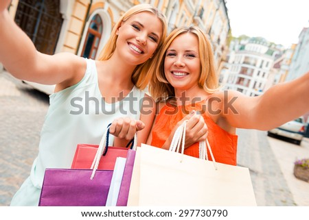 We love selfie! Happy mother and her daughter making selfie on camera and holding shopping bags while standing outdoors - stock photo