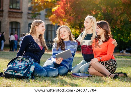 We love spending time together. Four happy caucasian young women spending time together while sitting in autumn park outdoors - stock photo