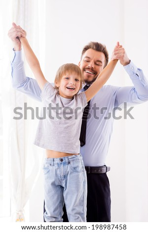We love spending time together! Happy father in formalwear having fun with his son at home - stock photo