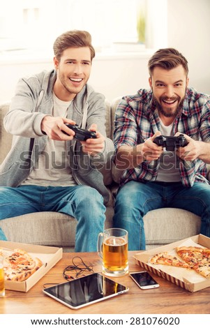 We love this game! Two cheerful young men playing video games while sitting on sofa - stock photo