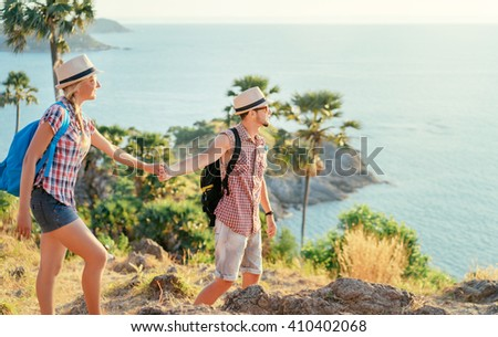 We love traveling and trekking! Caucasian young loving couple walking on mountains near the sea. - stock photo
