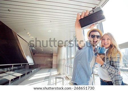 We love traveling! Vacation Selfie. Beautiful young loving couple making selfie by their camera while waiting for boarding in the airport. - stock photo