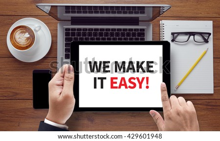 WE MAKE IT EASY! , on the tablet pc screen held by businessman hands - online, top view - stock photo
