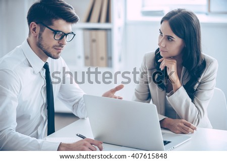 We need to change this numbers. Two coworkers discussing something and using laptop while sitting at the office table - stock photo