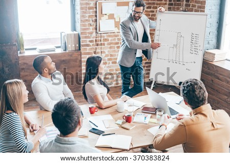 We should use this strategy! Top view of handsome young man in glasses standing near whiteboard and pointing on the chart while his coworkers listening and sitting at the table in office - stock photo
