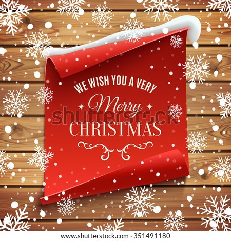 We wish you a very Merry Christmas, greeting card. Red, curved, paper banner on wooden planks with snow and snowflakes. - stock photo