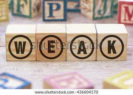 WEAK word written on wood cube - stock photo