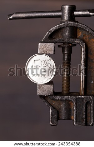 Weakening of the russian ruble concept. Coin in old vise - stock photo