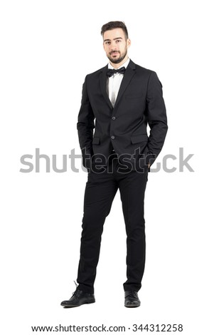 Wealthy confident relaxed young man in tuxedo looking at camera with hands in pockets. Full body length portrait isolated over white studio background. - stock photo