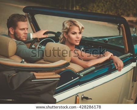 Wealthy couple in a classic convertible  - stock photo