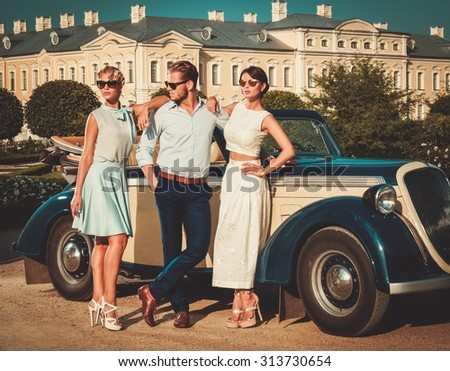 Wealthy friends near classic convertible  - stock photo