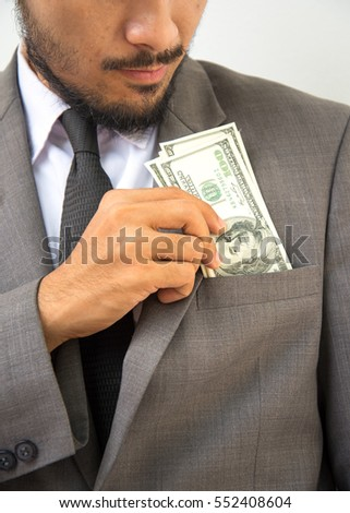 Wealthy handsome man. Close-up of young man putting money in his pocket while standing against grey background