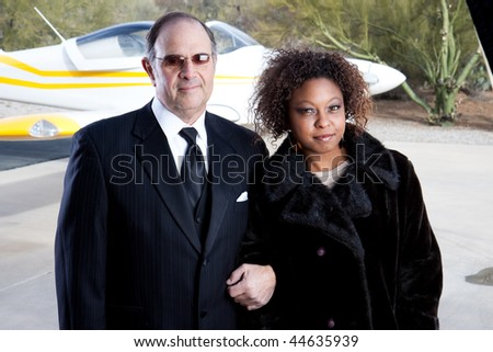 wealthy interracial couple and private plane