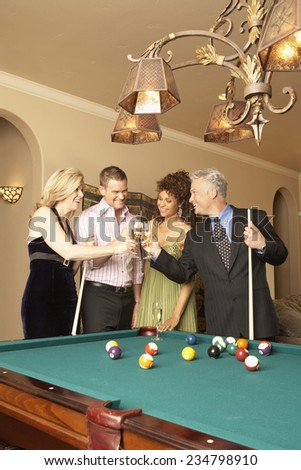 Wealthy People Making Toast by Pool Table - stock photo