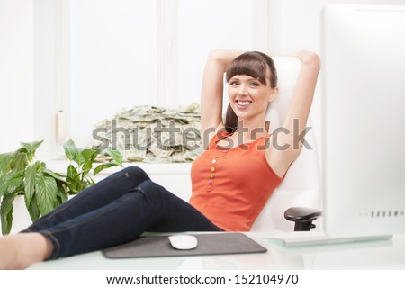 Wealthy woman. Happy young woman sitting at her working place while a stack of money lying on the window sill