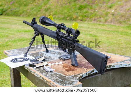 weapon and target sign on a table - stock photo