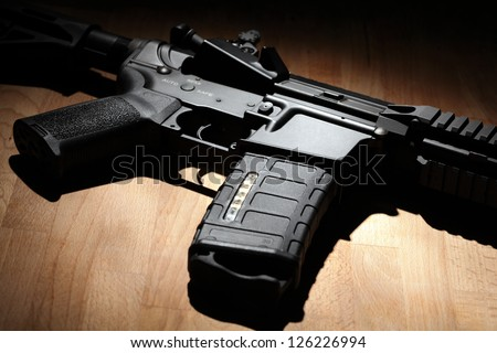 Weapon series. Custom build AR-15 (M4A1) carbine on a wooden surface. Studio shot. - stock photo