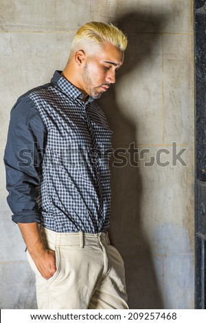 Wearing a black patterned shirt, yellow pants, a young man with beard, yellow hair is leaning against the wall outside a metal gate, hands in pockets, looking down, sad, thinking. - stock photo