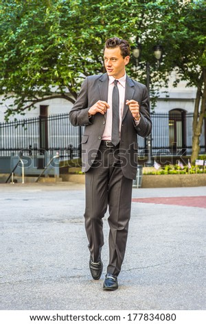 Wearing a black striped jacket, pants, tie, leather shoes,  a young businessman is walking outside an office building. / Businessman Walking  - stock photo